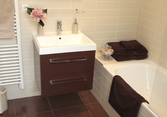 bathroom equipped with a bathtube, a wash hand basin with drawers, towel hang dryer and Hair dryer
